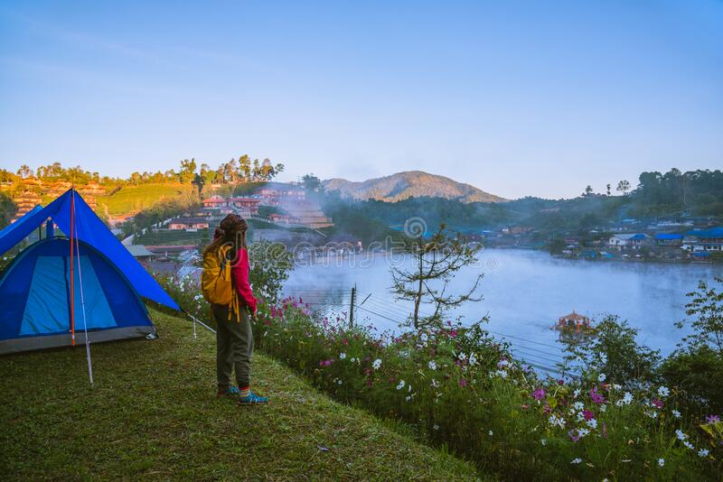 The girl set up a camp on the mountain near the lake, Camping Travel Concept, natural rhythms, fog in the winter.  stock photos