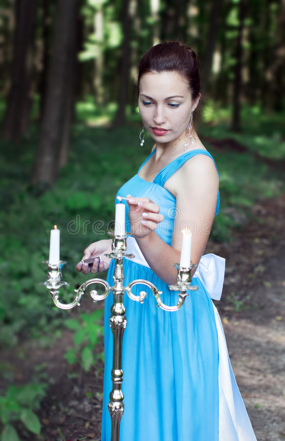 Girl sets fire three candles on a silver candlestick in a forest stock photo