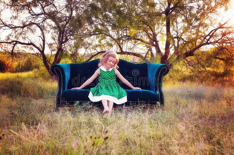 Girl on a settee in the countryside. Cute young girl sat on a settee in the countryside with a sunset in the background royalty free stock photos