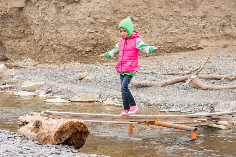 Girl seven years is on rickety bridge over creek arms outstretched for balance stock photo