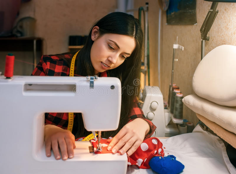 Girl sewing on a sewing machine stock photo