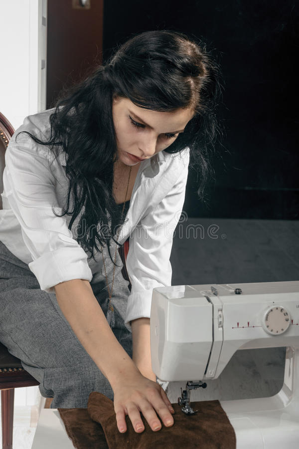Girl sews clothes. She is dressed in a white shirt stock photo