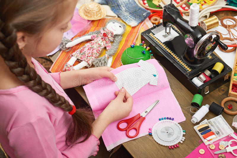 Girl sews doll clothes, top view, sewing accessories top view, seamstress workplace, many object for needlework, handmade and hand stock photos