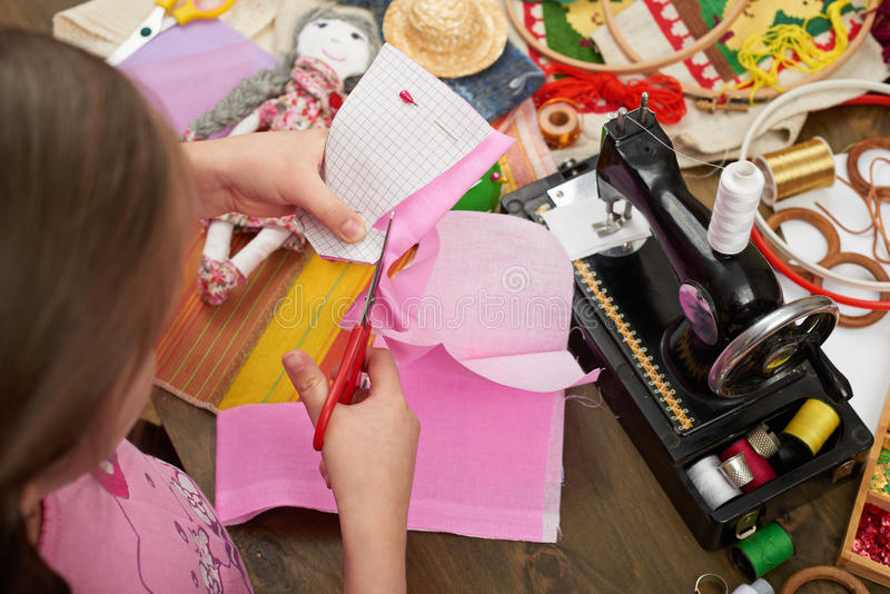 Girl sews doll clothes, top view, sewing accessories top view, seamstress workplace, many object for needlework, handmade and hand stock image