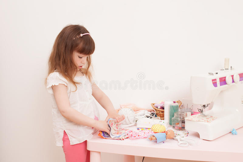Girl sews dress dolls from pieces of fabric. The girl chooses a piece of fabric for doll clothes, playing dress up. Next sewing machine, thread, buttons, needles royalty free stock photos