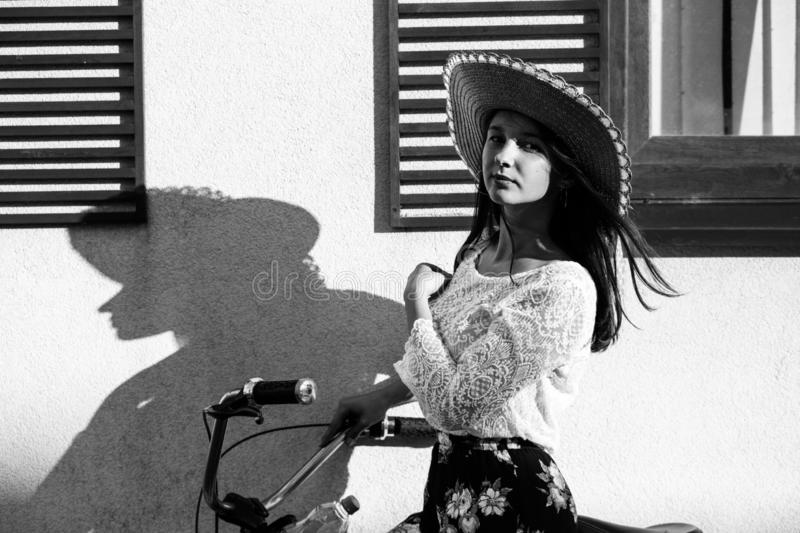 Girl with shadow. Attractive serious girl in hat near wall standing near wall with bicycle, looking at camera, monochrome royalty free stock photo