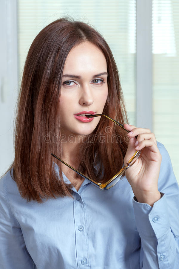 Girl in shirt is holding glasses in mouth royalty free stock image
