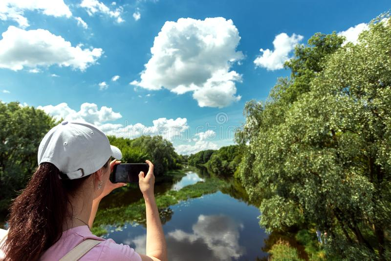 Girl shoots a beautiful landscape on a smartphone. Female tourist takes a photo from a mobile phone camera. Travel, vacation,. Vacation, tourism stock image