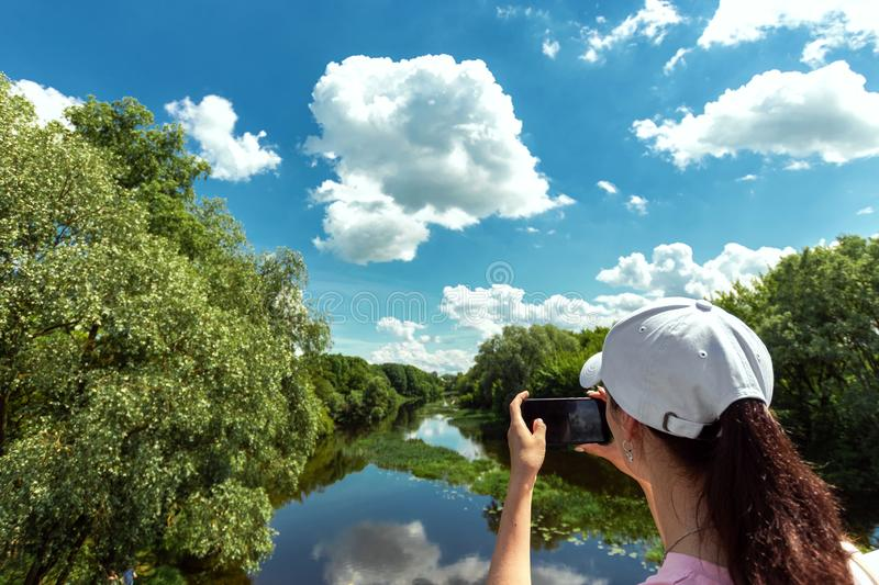 Girl shoots a beautiful landscape on a smartphone. Female tourist takes a photo from a mobile phone camera. Travel, vacation,. Vacation, tourism royalty free stock image