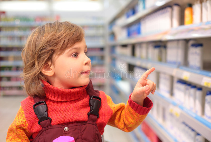 Girl in shop of household cosmetics. Little girl in shop of household cosmetics royalty free stock image