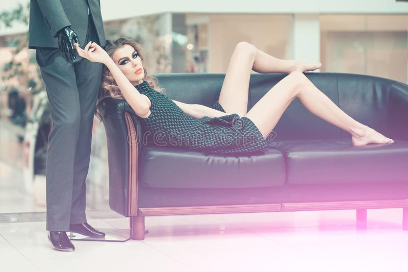 Girl shopaholic tired shopping. Woman shopper relax on sofa with fashion mannequin in shop. Shop, shopping, sale. Fashion, style, vogue. Beauty, look makeup royalty free stock image