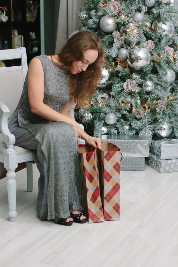 Girl with shopping bags near the christmas tree royalty free stock photos