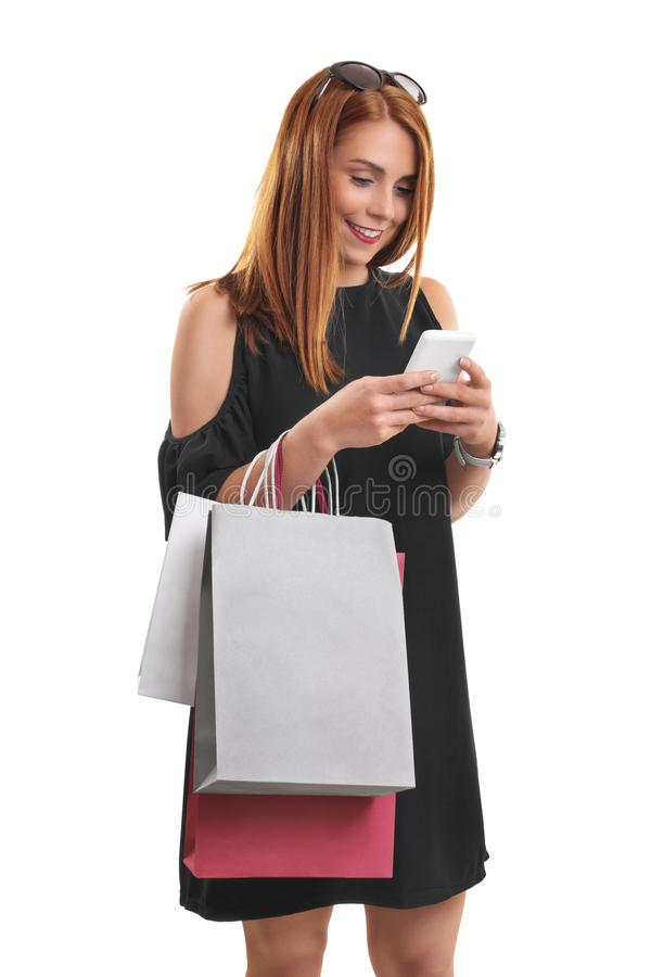 Girl with shopping bags typing on her phone royalty free stock image