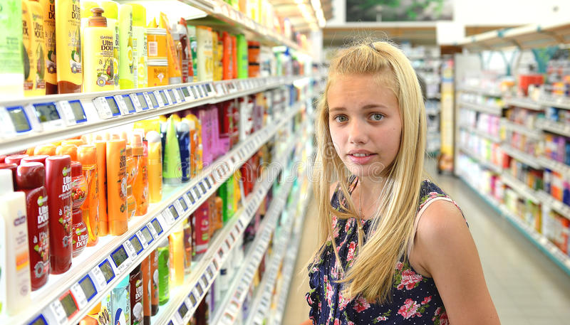 Girl shopping for beauty products. Young girl stood in supermarket store aisle shopping for beauty products stock photos