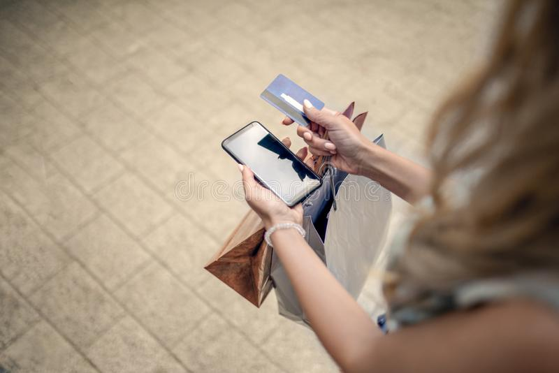 Woman in shopping. Credit card, phone, shopping, lifestyle concept. Online shopping. Girl in shopping. Blonde woman with shopping bags, credit card and phone stock images