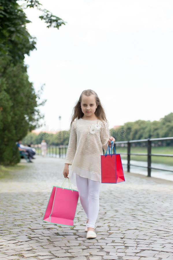 Girl shopping on calm face carries bags, urban background. Kid girl with long hair fond of shopping. Fashionista girl. Girl shopping on calm face carries stock photos