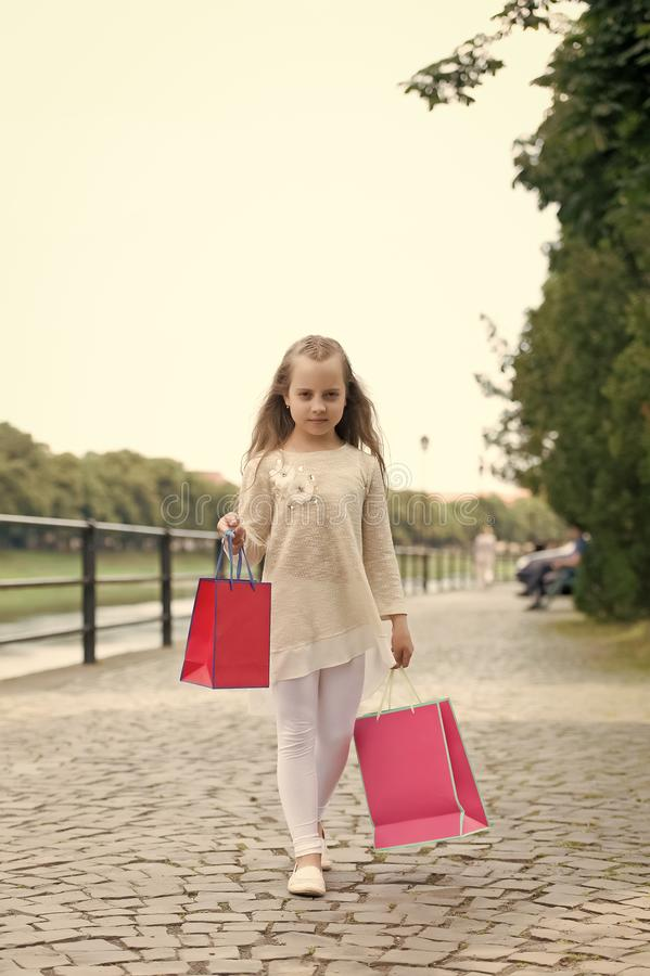 Girl shopping on calm face carries bags, urban background. Kid girl with long hair fond of shopping. Fashionista girl. Girl shopping on calm face carries royalty free stock photo