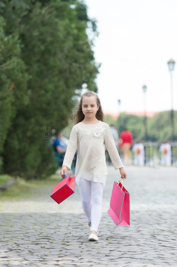 Girl shopping on calm face carries shopping bags, urban background. Kid girl with long hair fond of shopping. Shopping. Concept. Girl likes to buy clothes stock photos