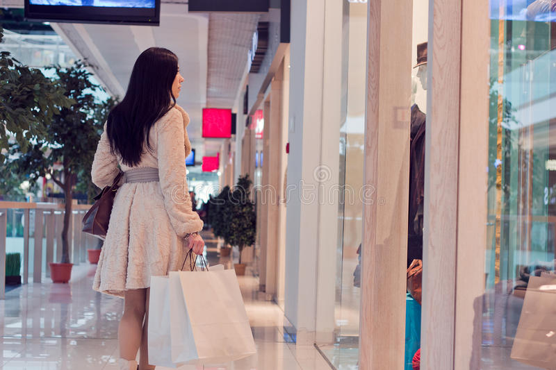 Girl in the shopping centre with shopping bags royalty free stock images