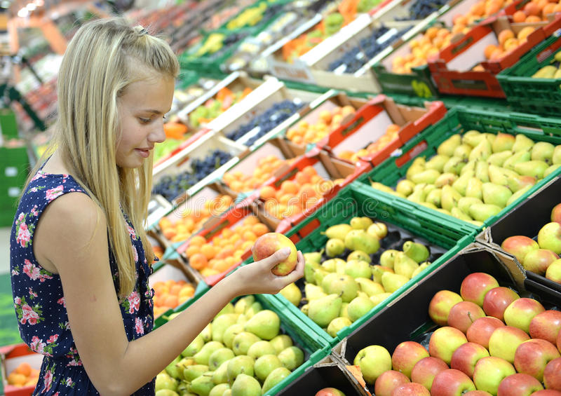 Girl shopping for fruit. Young blond girl shopping for fruit in supermarket royalty free stock image