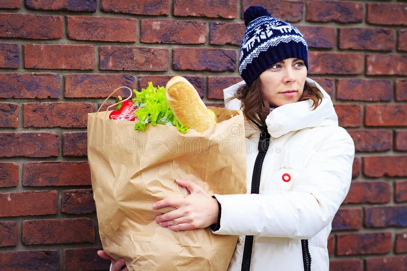 Girl shopping at grocery store. Attractive woman with paper food product package. woman holding grocery shopping bag stock photo