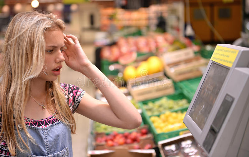 Girl shopping in grocery store. Young teenage girl with confused expression, shopping in a grocery store royalty free stock photos