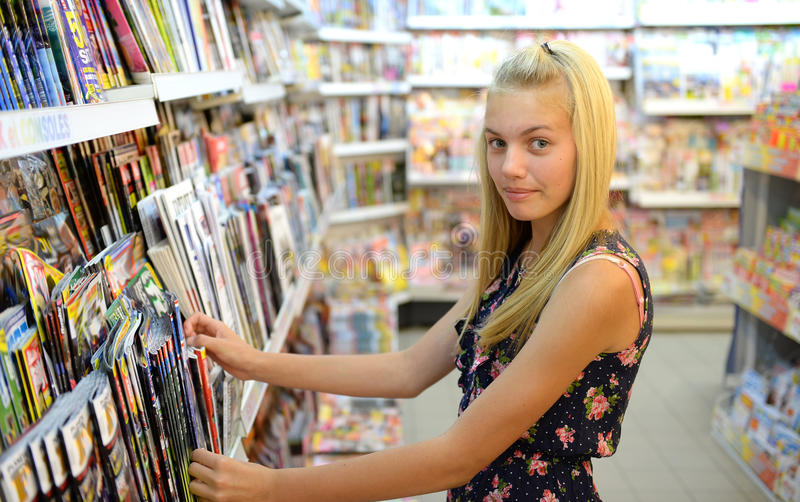 Girl shopping for magazine. Young blond girl shopping for magazines in shop or store stock images