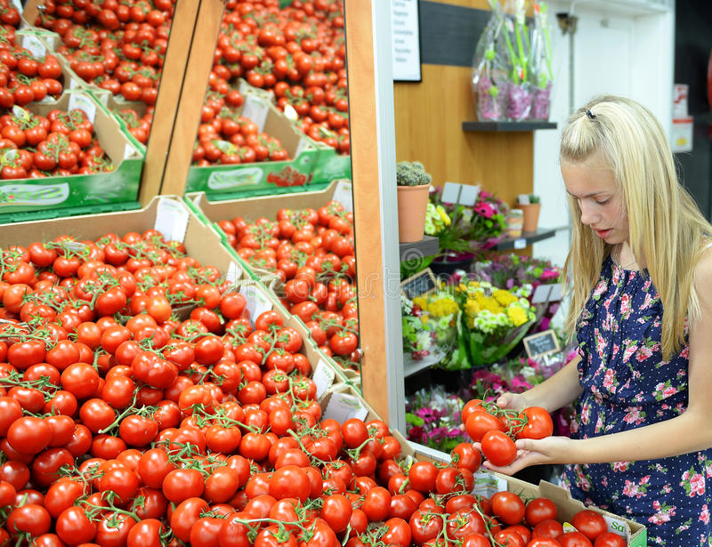 Girl shopping for tomatoes. Young blond girl shopping for tomatoes in supermarket store royalty free stock photo