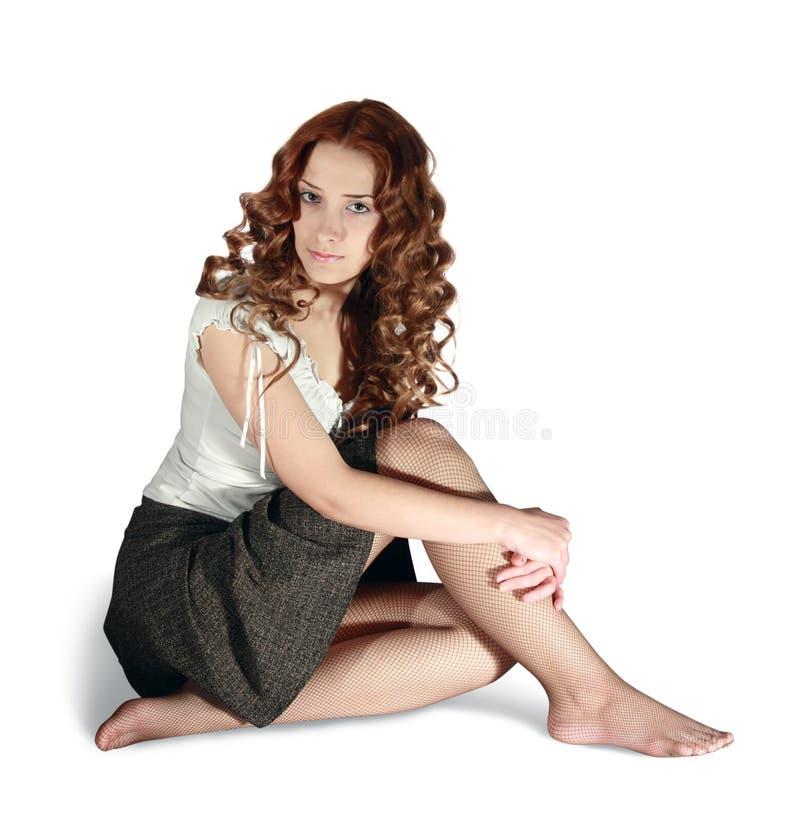 Girl in short skirt on white background. Sexual long-haired girl in skirt on white stock images