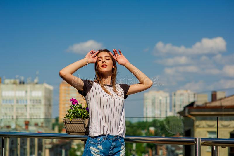 Girl in shorts on the balcony in a cafe. Summer portrait of young stylish girl posing on balcony, mini denim shorts stock images