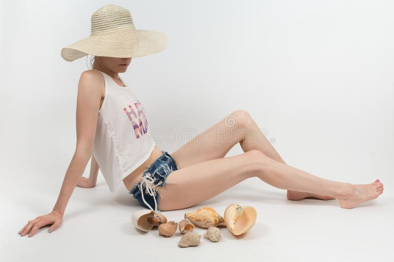 The girl in shorts and hat covering her face sitting on white background isolated stock image
