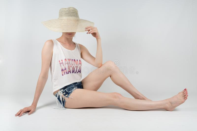 The girl in shorts and hat covering her face sitting on white background isolated royalty free stock image