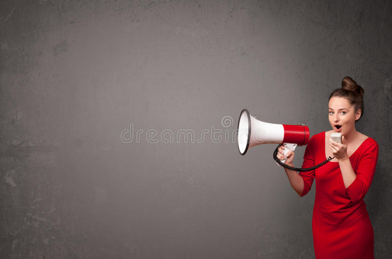 Girl shouting into megaphone on copy space background. Pretty girl shouting into megaphone on copy space background royalty free stock photo