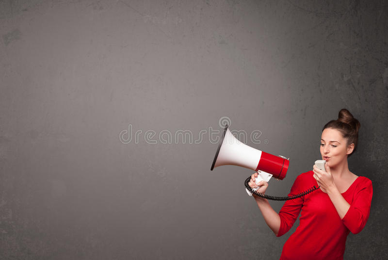 Girl shouting into megaphone on copy space background. Pretty girl shouting into megaphone on copy space background royalty free stock images