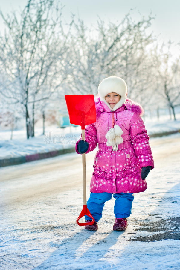 The girl with a shovel for snow royalty free stock image