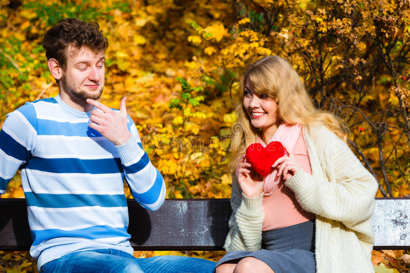 Girl show feelings to man in autumnal park. Accepting and sharing feelings. Confessing love and affection with romantic gesture. Positive reaction. Pair sit on royalty free stock photography