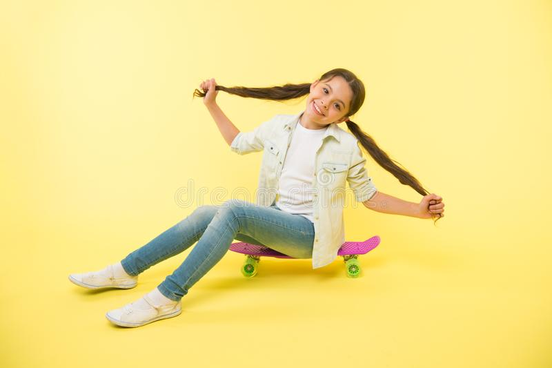 Girl show long ponytail hairstyle sit penny board yellow background. Child cute hairstyle ride penny board. Proud of. Long hair. Hairstyle for active leisure royalty free stock photo