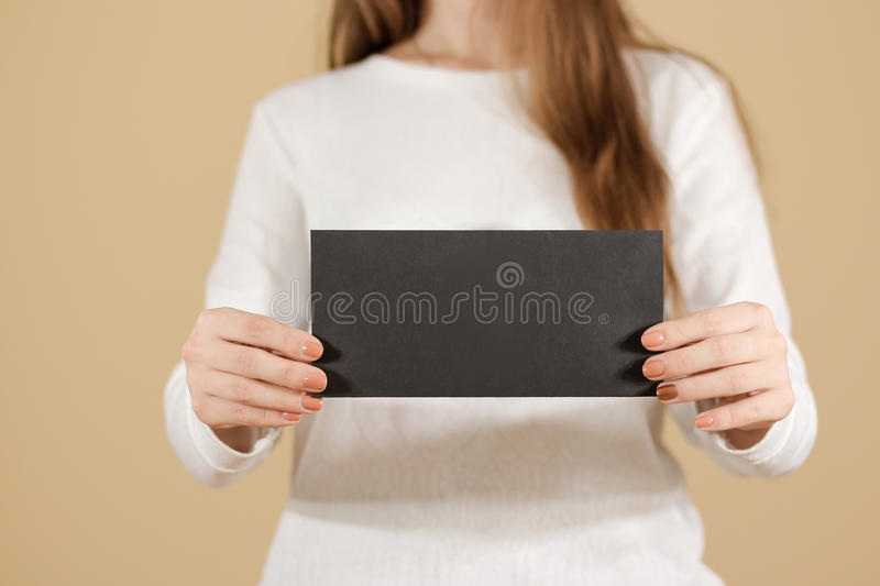 Girl showing blank black flyer brochure booklet. Leaflet present. Ation. Pamphlet hold hands. Woman show clear offset paper. Sheet template. Booklet design sheet royalty free stock photography