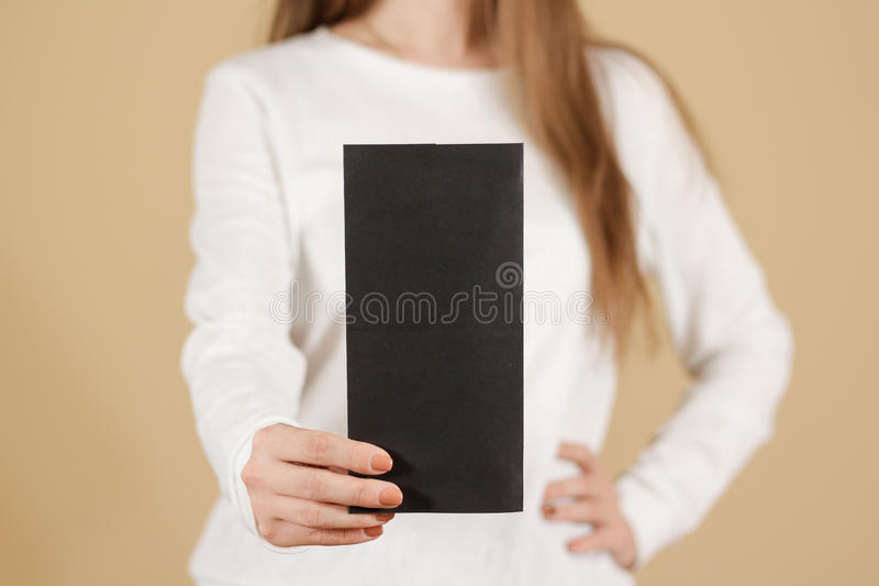 Girl showing blank black flyer brochure booklet. Leaflet present. Ation. Pamphlet hold hands. Woman show clear offset paper. Sheet template. Booklet design sheet stock photography