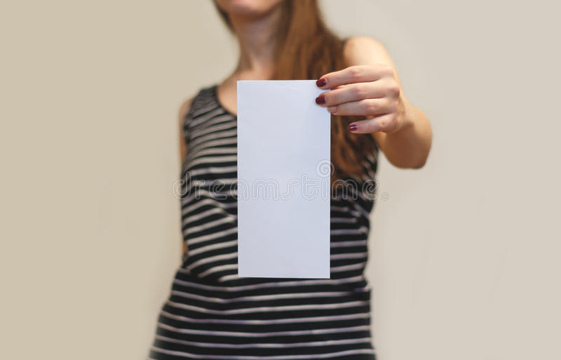Girl showing blank white flyer brochure booklet. Leaflet present. Ation. Pamphlet hold hands. Woman show clear offset paper. Sheet template. Booklet design sheet royalty free stock images