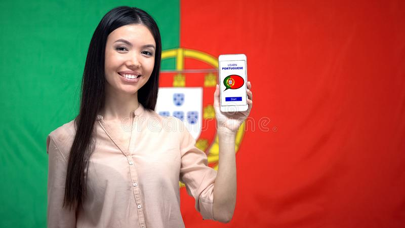 Girl showing cellphone with learn Portuguese app, flag on background, education. Stock photo royalty free stock photos