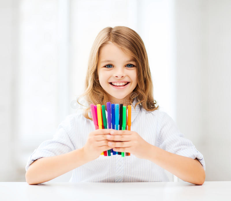 Girl showing colorful felt-tip pens. Education and school concept - little student girl showing colorful felt-tip pens at school royalty free stock photography