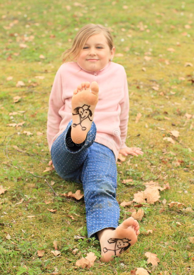 Girl showing drawen hearts on soles stock images