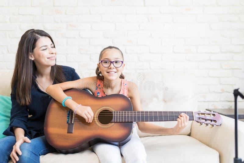 Girl Showing Guitar Skills To Teacher On Sofa royalty free stock image