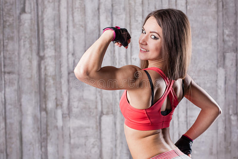 Girl showing her muscles. At gym royalty free stock photo