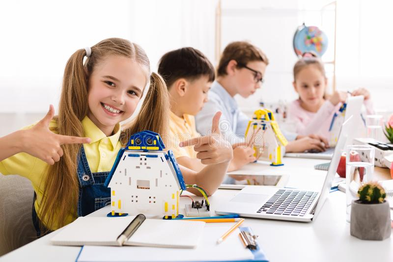 Girl showing her robot. Proud student of her project royalty free stock photography