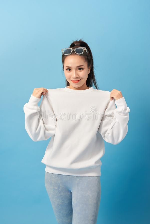 Girl showing new t-shirt she bought on sale, being pleased and happy over light blue background stock image