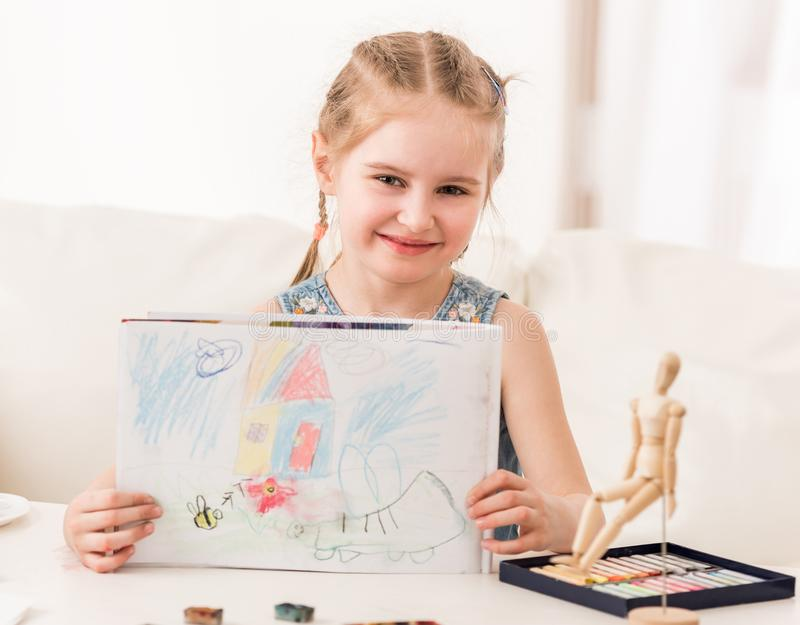 Girl showing pastel drawing. Little girl showing her beatiful drawing, made with dry pastel stock images