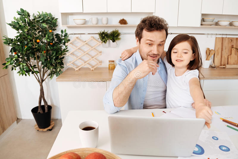 Girl showing something amusing to her father on laptop. Curious glances. Smiling little girl hugging her father with one hand and pointing at something amusing royalty free stock photos
