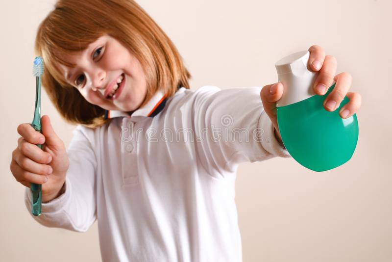 Girl showing toothpaste and toothbrush on brown background isolated stock images